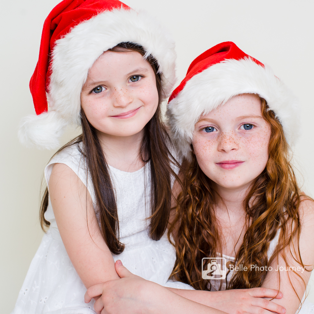 Sisters cuddling each other Christmas Santa hats pic
